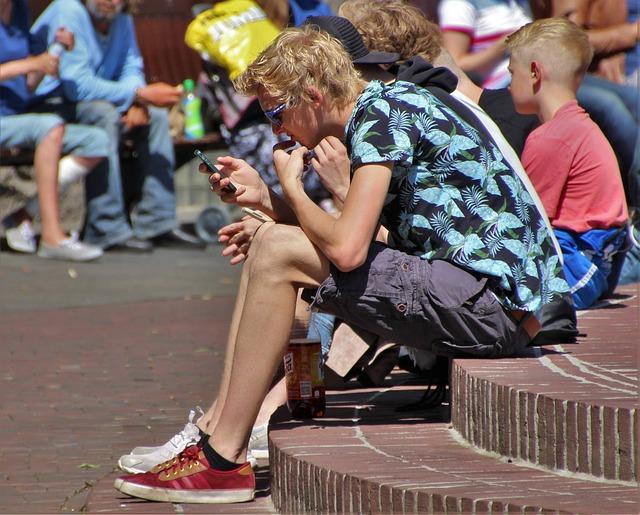 chlapci sedící na veřejném prostranství s telefonem